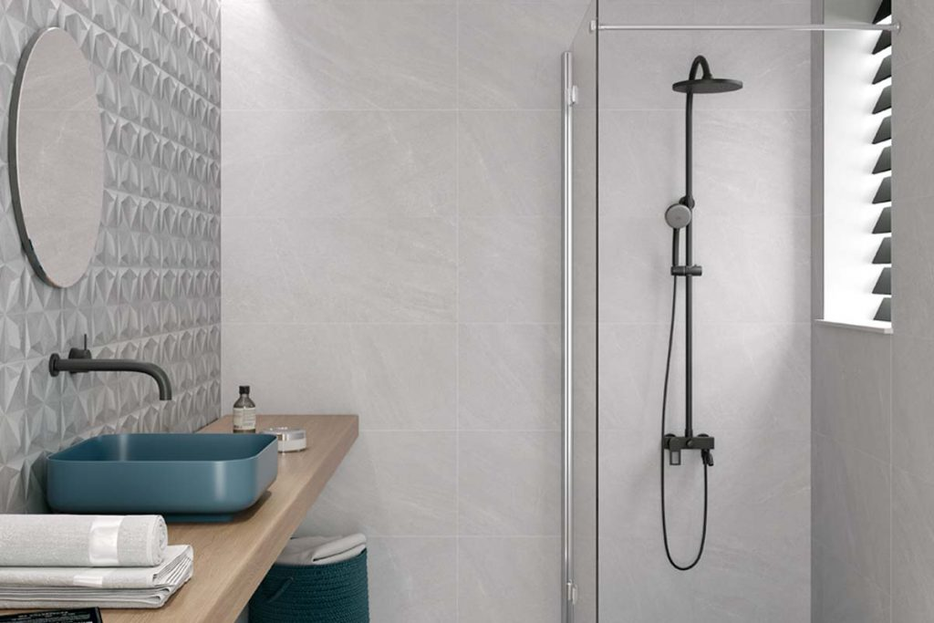 Bathroom grey stone effect tiles with shower and decor tiles.