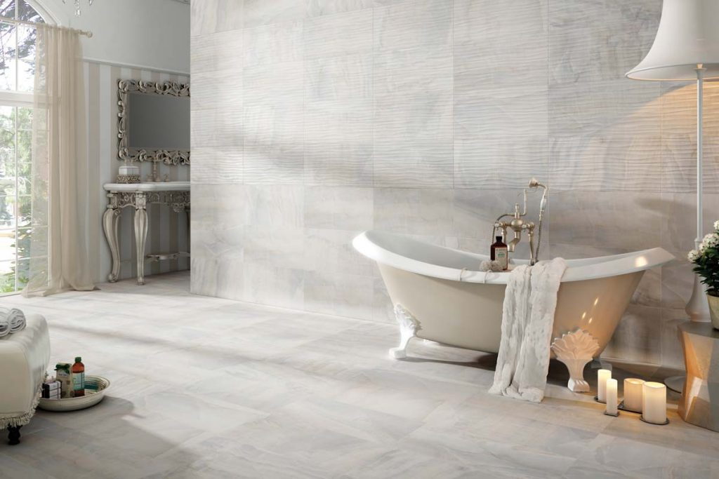 Marble effect wall and floor tiles in bathroom with decor.