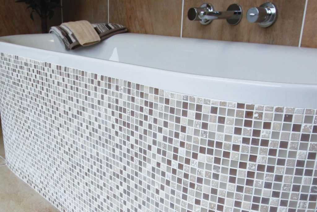 Mosaic glass and natural stone tiles in beige, brown and cream in a bathroom.