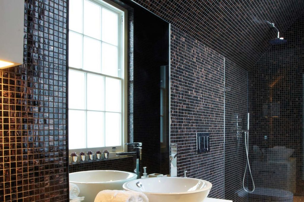 Mosaic square glass tiles with a gold vein running through. Shown here in a bathroom.