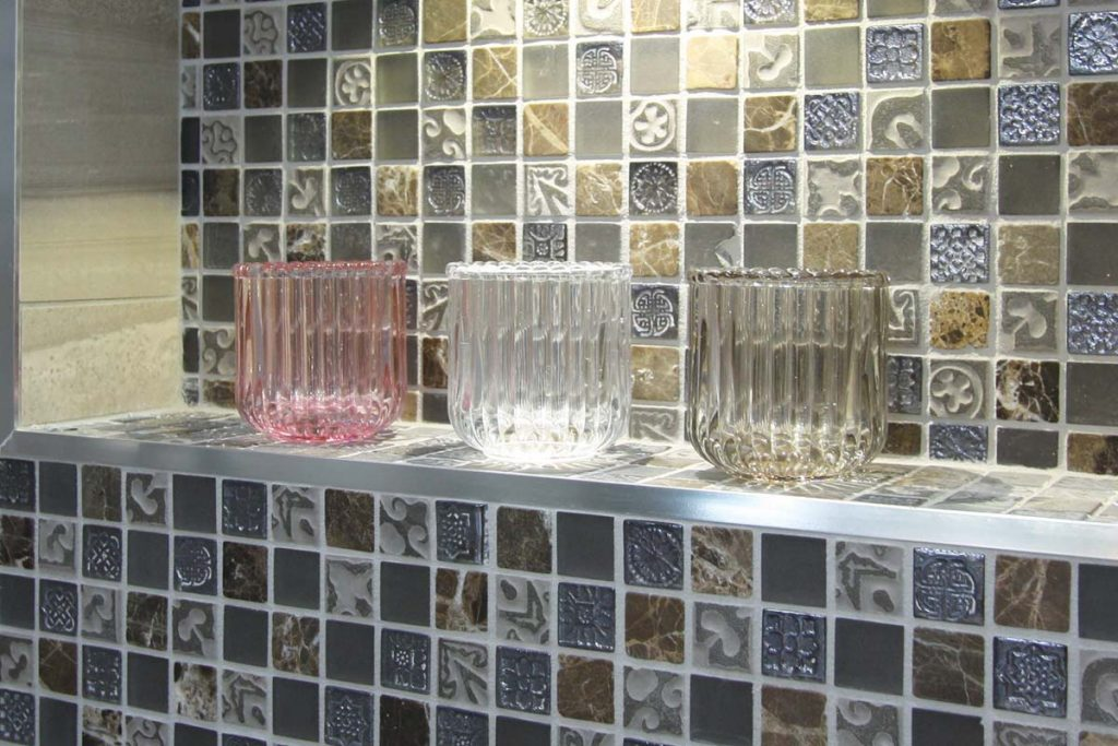Mosaic square glass, natural stone and porcelain mix tiles with a glittery effect. Shown here in a bathroom.