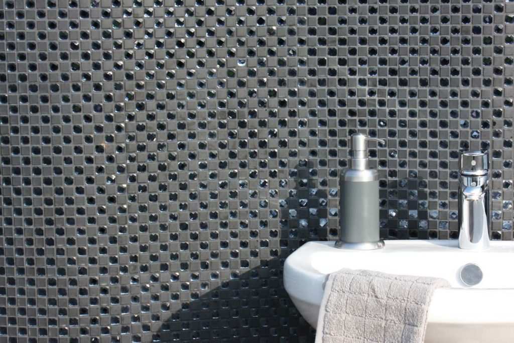 Mosaic cut and frosted glass in a checker board pattern black tiles, shown here in a bathroom.