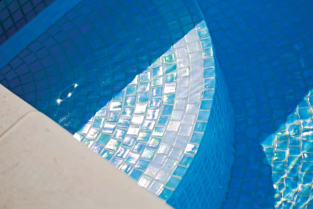 Mosaic square glass tiles in sky blue and white, shown here in a swimming pool.