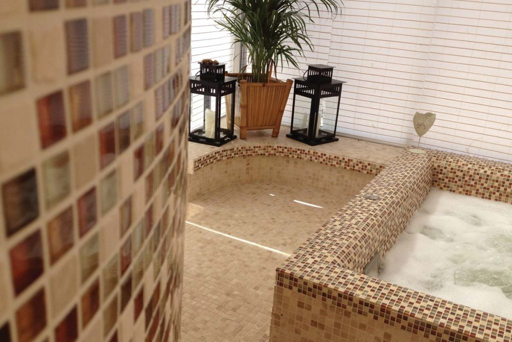 Mosaic glass and natural stone tiles in copper bronze in a spa.