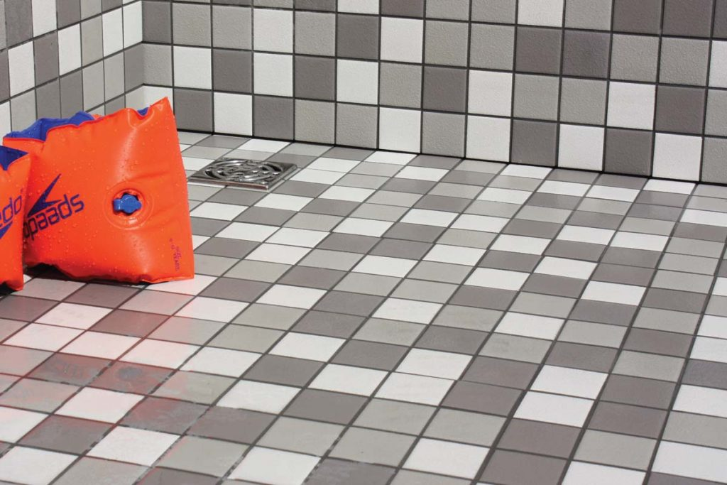Mosaic glazed ceramic tiles in white and grey in a shower.