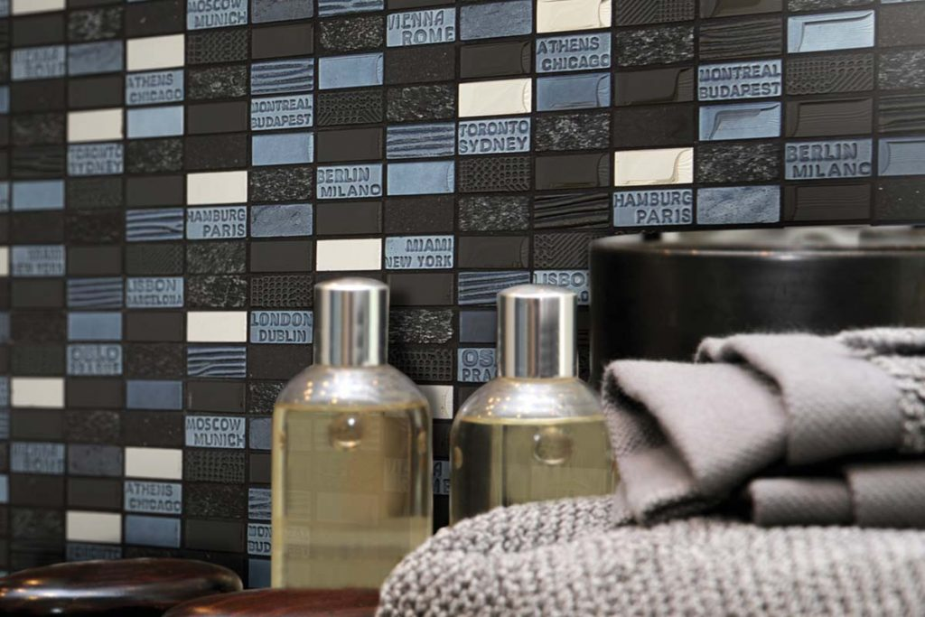 Mosaic glass and natural stone mix hexagonal tiles in white, black and silver with text printed on the mosaic, shown in a bathroom.