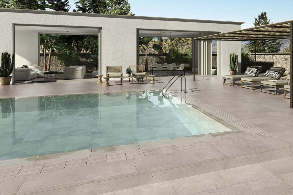 Outdoor beige stone effect tiles near swimming pool.