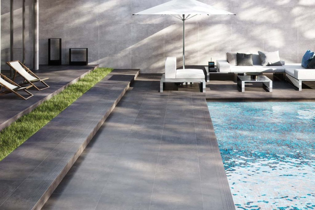 Outdoor dark grey stone effect tiles near swimming pool.
