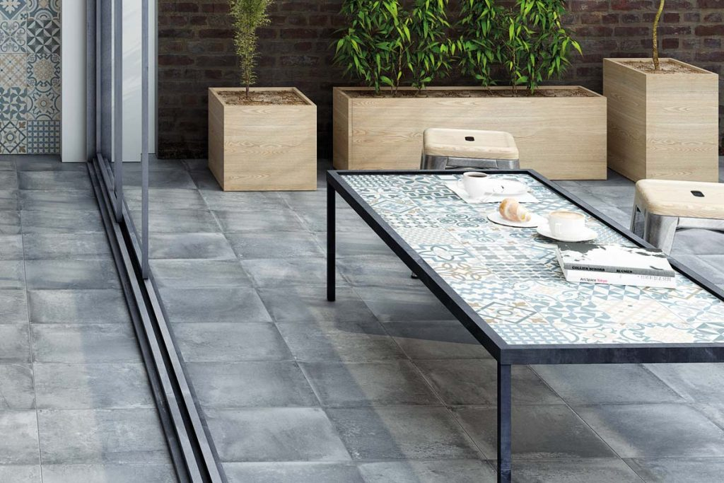 Outdoor grey stone effect tiles with outdoor seating.