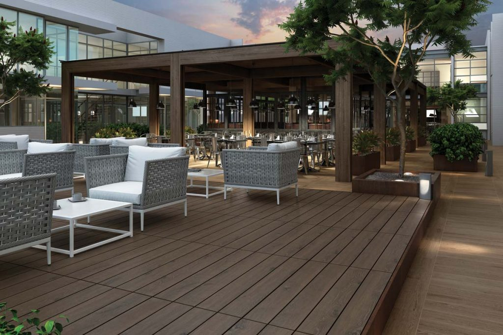 Outdoor dark wood effect tiles on decking with outdoor seating.