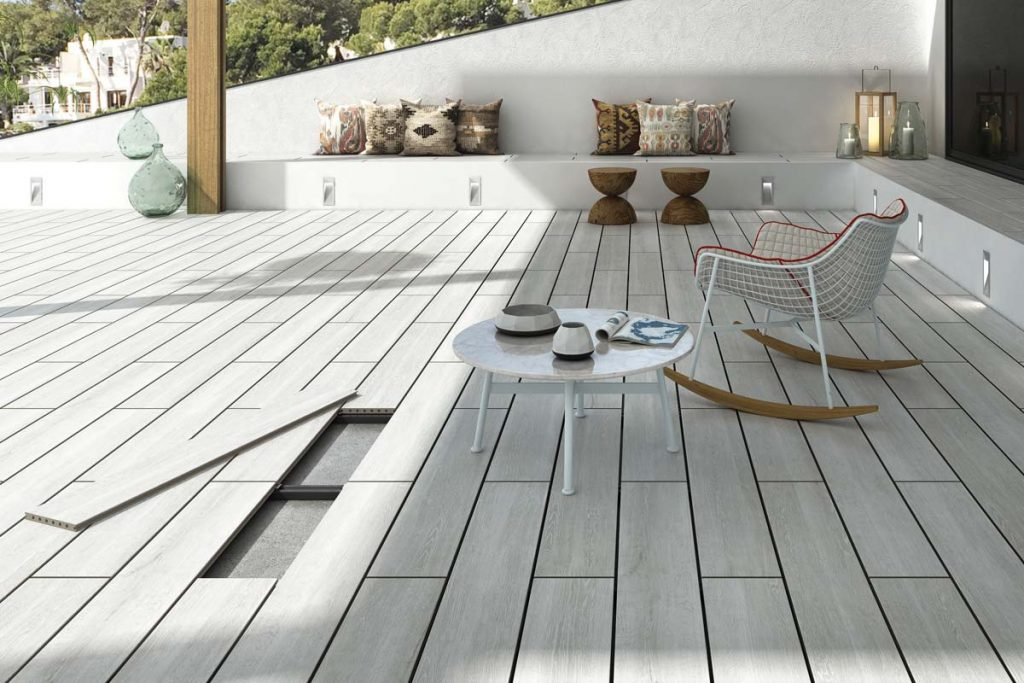 Outdoor light grey wood effect tiles raised flooring system on decking with outdoor seating.