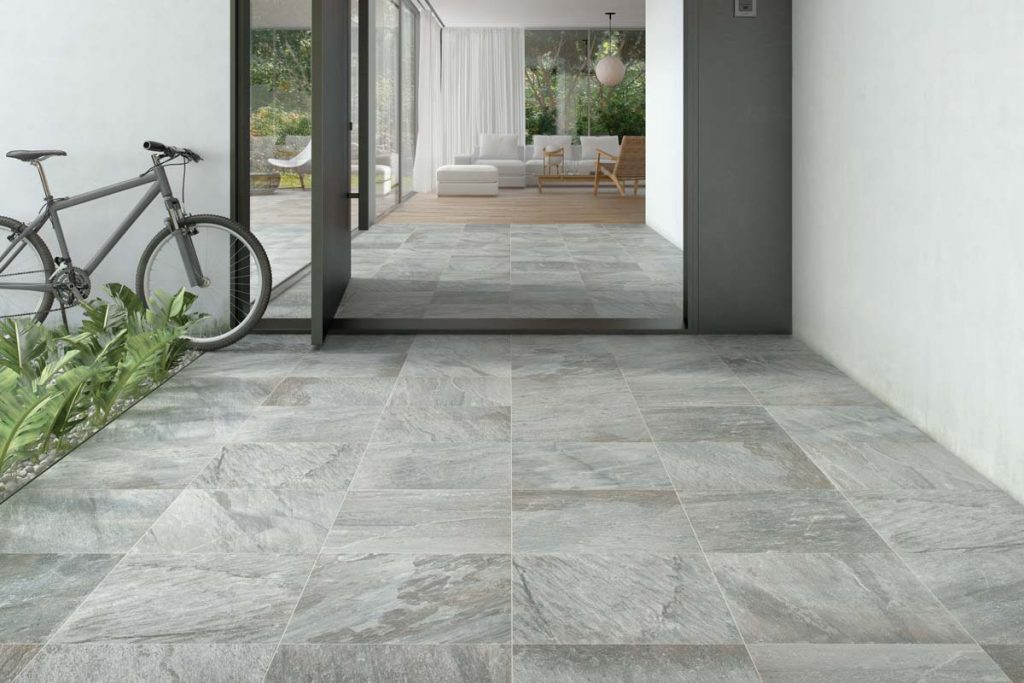 Outdoor grey stone effect tiles with bike.