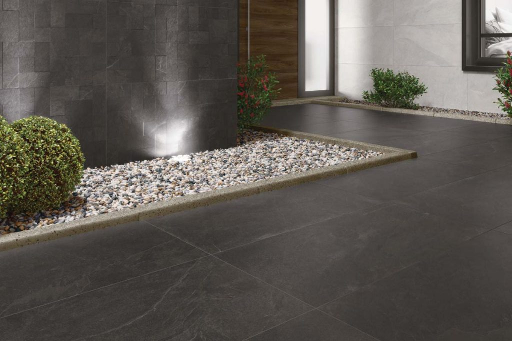 Outdoor dark grey stone effect tiles with feature garden light and gravel.