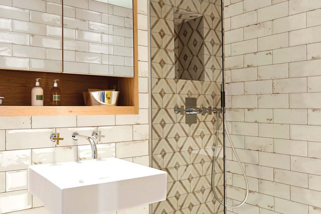 Vintage glazed ceramic hexagonal pattern wall tiles. Glazed cream and decor pattern, displayed here in a bathroom.