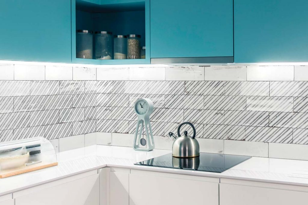 Vintage glazed ceramic hexagonal pattern wall tiles. Glazed white and stripe decor pattern, displayed here in a kitchen.
