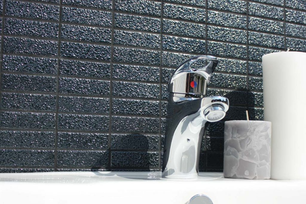 Contemporary glass ceramic mosaics in a rectangular shape. Black with a dewdrop finish, displayed here in a bathroom.