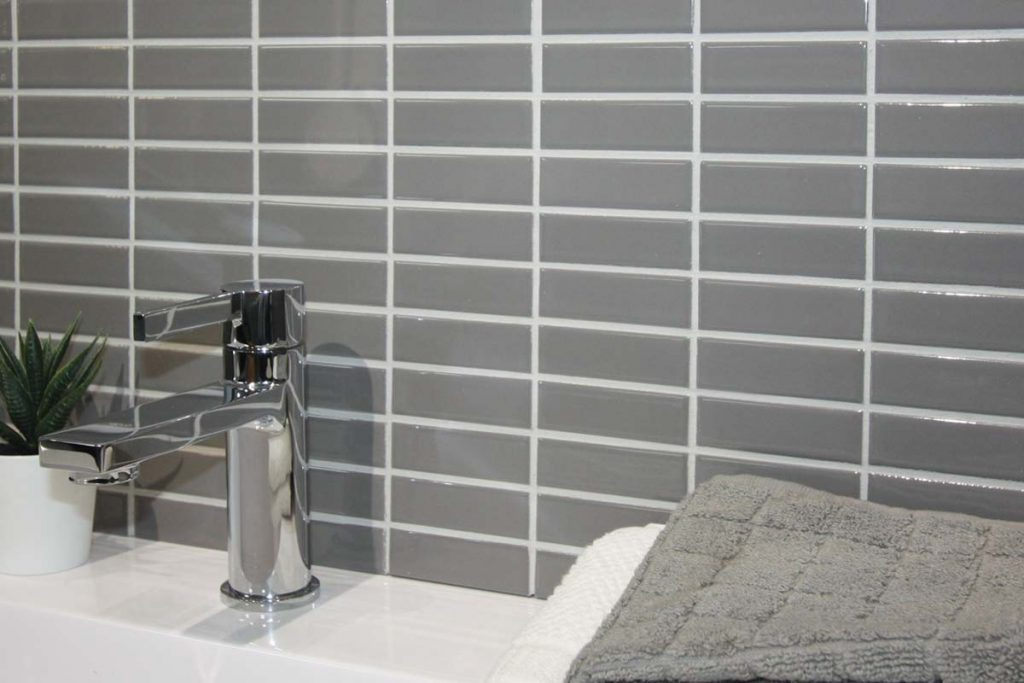 Contemporary glass ceramic mosaics in a rectangular shape. Light grey with a gloss finish, displayed here in a bathroom.