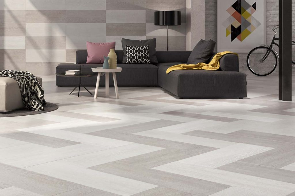 Glazed porcelain rectangular wood effect tiles. White with shades of grey. Displayed here in a front room.