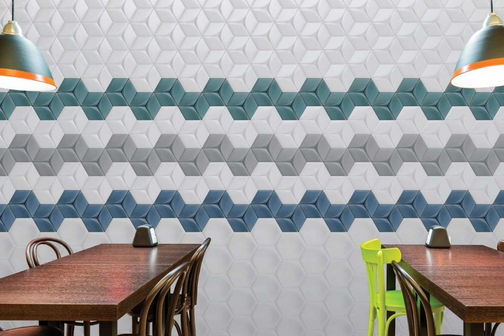 Glazed ceramic hexagon shaped tiles with a 3D hexagon decor. Pastel shades of green, grey and white. Displayed here in a kitchen.