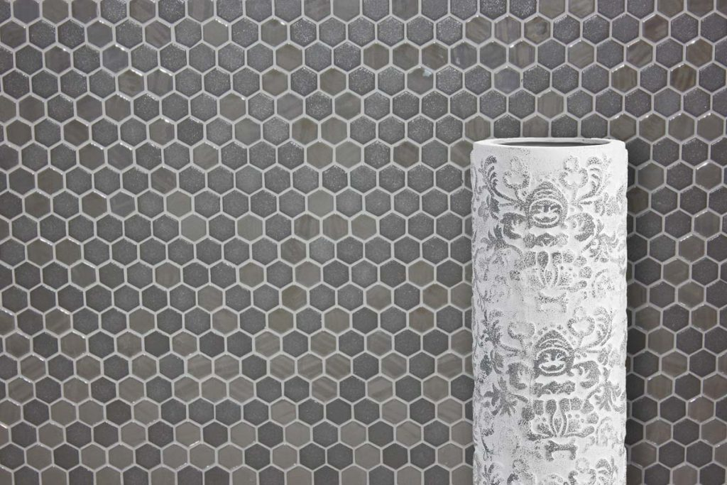 Glass mosaics in a hexagonal shape. Different shades of grey, displayed here in a hallway.
