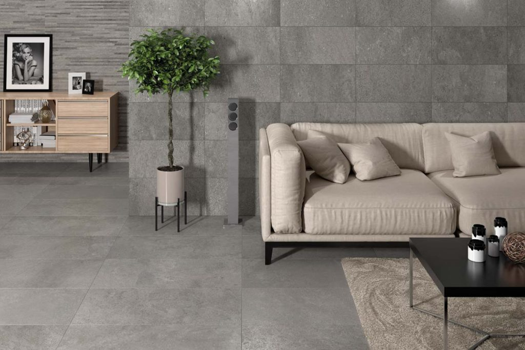 Glazed Ceramic wall and Glazed Porcelain floor stone effect tiles in a grey shade. Displayed in a living room.