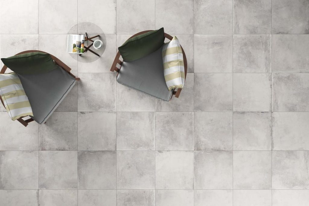 Glazed Porcelain concrete effect tiles, light grey with a matt finish. Displayed here in a living room.
