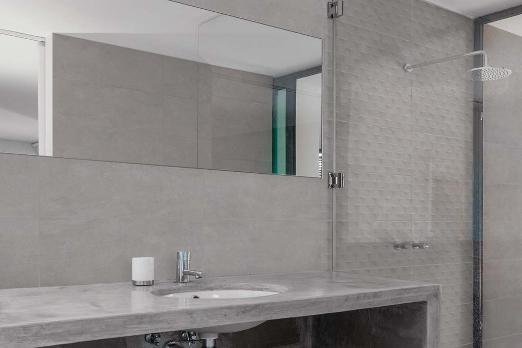 Glazed Ceramic concrete effect tiles, grey with a matt finish and matching decor. Displayed here in a bathroom.
