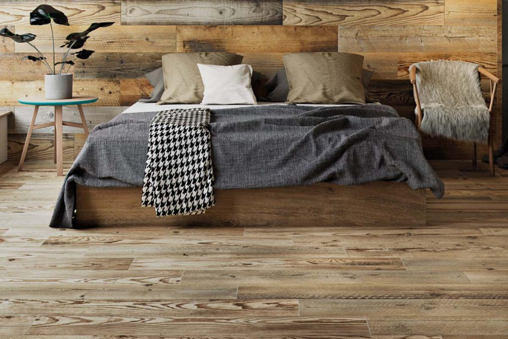 Glazed Porcelain wood effect tiles in rich brown. Displayed in a bedroom.