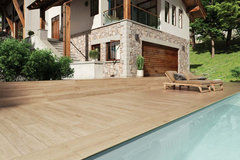 Glazed Porcelain wood effect tiles in light brown. Displayed outside around a swimming pool.