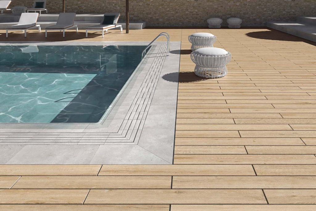 Glazed Porcelain wood effect tile decking system in light brown. Displayed outside around a swimming pool.