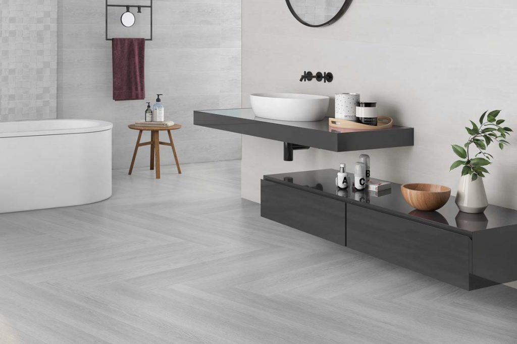 Glazed Ceramic wood effect tiles in a light grey. Displayed in a bathroom.