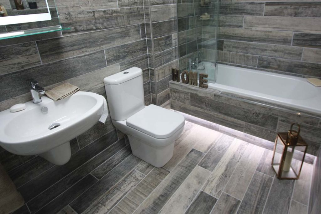 Glazed Porcelain wood effect tiles in a variety of grey shades. Displayed in a bathroom.